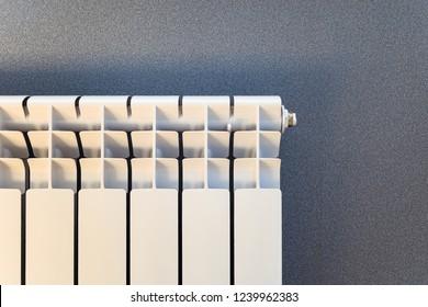 White radiator heating ona gray wall background