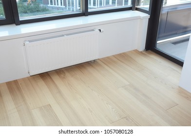 White radiator heating with thermostat for energy saving, wooden floor in the modern empty room.