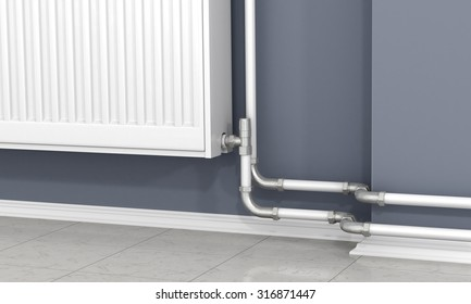 The white radiator and pipes of heating on the gray wall.