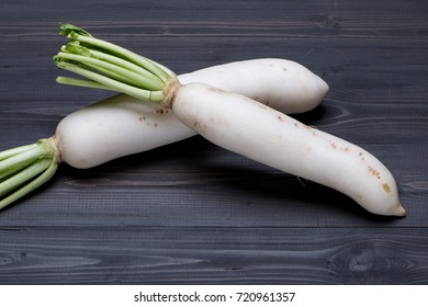 White Radish on dark wooden background with selective focus