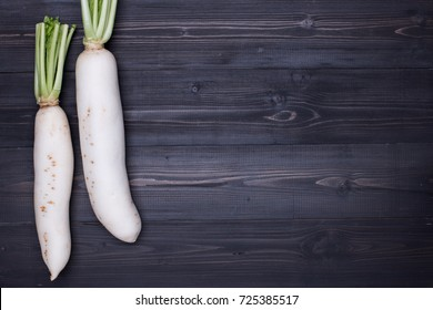White Radish on dark wooden background top view with copy space