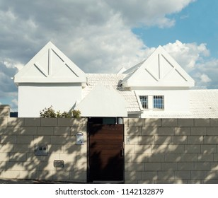 White random house under a sky full of clouds