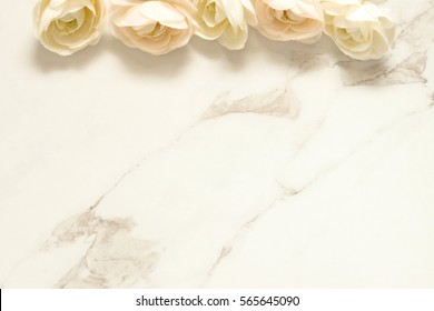 White ranunculous flowers border a white marble background with open space for copy.