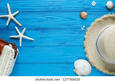White rattan bag, straw hat on blue background. bamboo trendy bag, starfish, shells. Summer fashion flat lay,   vacation, travel concept. Top view with copy space.