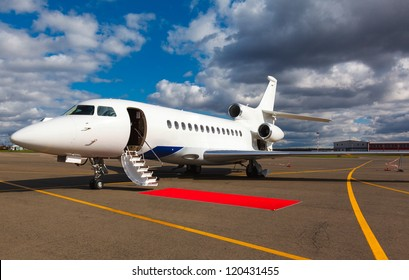 White reactive private jet, front landing gear and ladder on blue sky and clouds