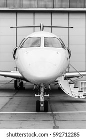 White reactive private jet, the front landing gear and a ladder on concrete Peron