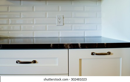 White rectangular backsplash with a white outlet, dark granite countertop. Light shining down from the top, top part of white drawers showing