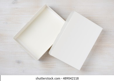 White rectangular empty open box, top view on wooden background