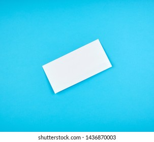 white rectangular paper envelope on a blue background, top view