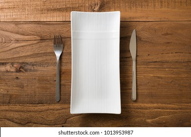 White rectangular Plate with fork and knife on brown wooden table background