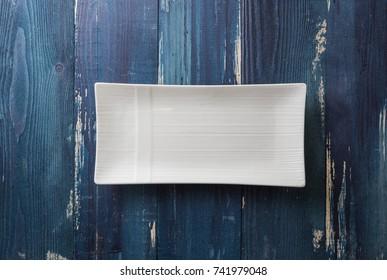 White rectangular Plate on ocean blue wooden table background