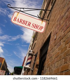 A white and red barber shop sign has rust above the striped pole