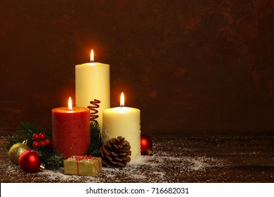 White and red candles with christmas decorations on rustic wooden background and snow, copy space. Greetings card template