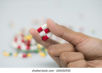 white red capsules pickup with two finger in the capsule bunch background