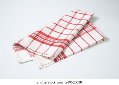 white and red checkered dishtowel on white background