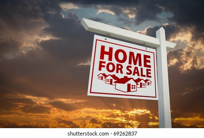 White and Red Home For Sale Real Estate Sign Over Beautiful Clouds and Sunset Sky.