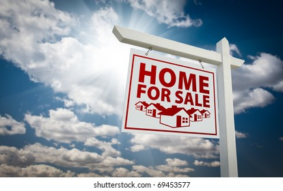 White and Red Home For Sale Real Estate Sign Over Beautiful Clouds and Blue Sky.
