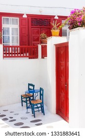 WHITE AND RED HOUSE IN GREEK ISLAND WITH BLUE TABLE AND CHAIRS
