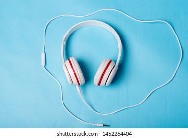 White red music headphones on technology background Notbook computer on a blue background. Happy holidays.