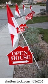 White and red open house signs with arrows and decorated with flags