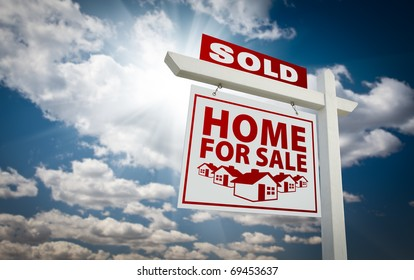 White and Red Sold Home for Sale Real Estate Sign Over Beautiful Clouds and Blue Sky.