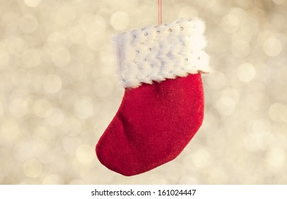 white and red stocking christmas ornament on golden background