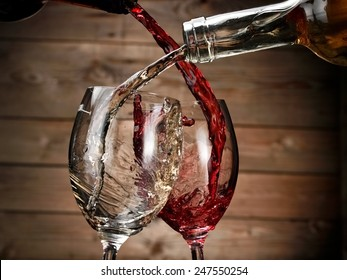 White and red wine pouring on wood background