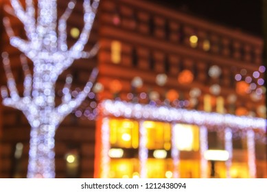 White, red, yellow Blurred lights of the urban Christmas and New Year illuminations on the background of architecture, abstract bokeh, defocused. Dnepr city, Ukraine, Dnepropetrovsk, Dnipropetrovsk