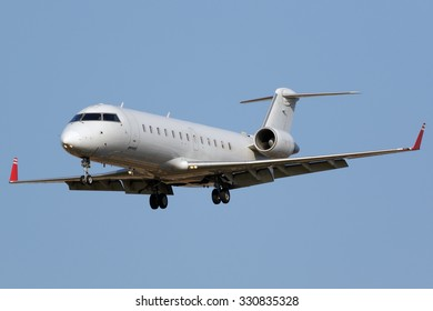White regional jet airplane approaching runway