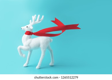 White reindeer with red ribbon on blue background. Christmas or New Year minimal concept.