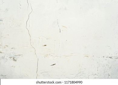 white relief texture of an old wall with potholes and fissure, close-up architecture abstract background