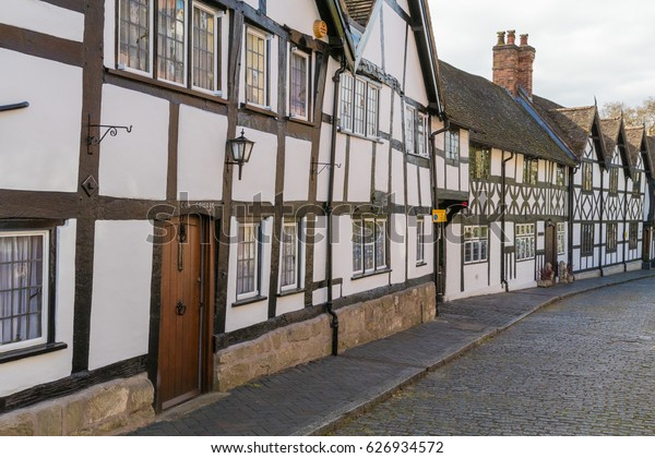 White render and black timber Ancient Tudor houses on the medieval Mill Street, below Warwick Castle, Mill St, Warwick, Warwickshire, United Kingdom, UK, April 2017