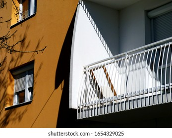 white residential balcony of modern design with curved white steel bar balustrade in orange brown stucco exterior wall. modern architecture concept. in textured stucco exterior wall field color