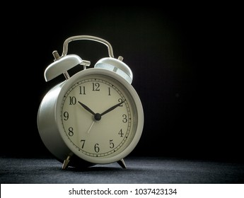 White retro alarm clocks on black background