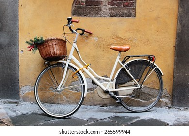 White retro bicycle with wicker brown basket standing at the wall, Italy