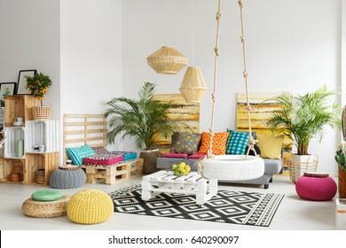 White, retro living room with pallet furniture and wheel swing