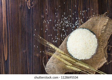 White rice in bowl and ear of paddy on wooden table.