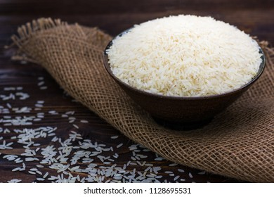 White rice in bowl on wooden table.
