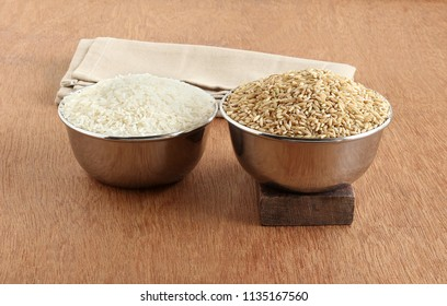 White rice and brown rice in steel bowls. Brown rice is said to be a superior food than its white counterpart, because of high fiber, magnesium and antioxidant.