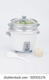 white rice cooker with accessory to cook steamed vegetables