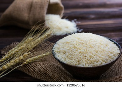 White rice and ear of paddy on wooden table.