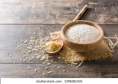 White rice flour in a bowl on wooden table. Copyspace