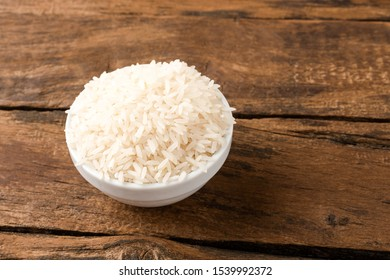 White rice grains in bowl on vintage wooden background