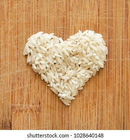 White rice grains in heart shape on wooden cutting board, in square format for social media, banners, and backgrounds.