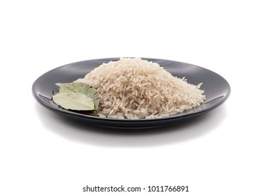 White rice on the black plate with dried laurel leaf. Isolated