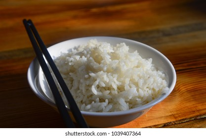 White rice on bowl with chopsticks on wooden table.