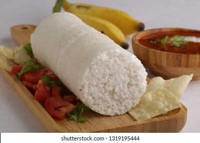 White Rice Puttu on wooden serving board with banana, kadala/bengal gram ,pappadam as side dish with white background