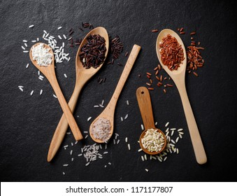 White rice and Raw rice in wooden spoon over black desk background