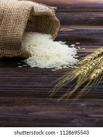 White rice in sack and ear of paddy on wooden table.