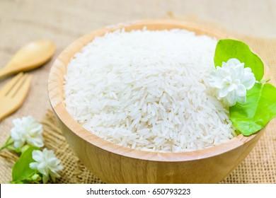 white rice (Thai Jasmine rice) with jasmine flower in wooden bowl